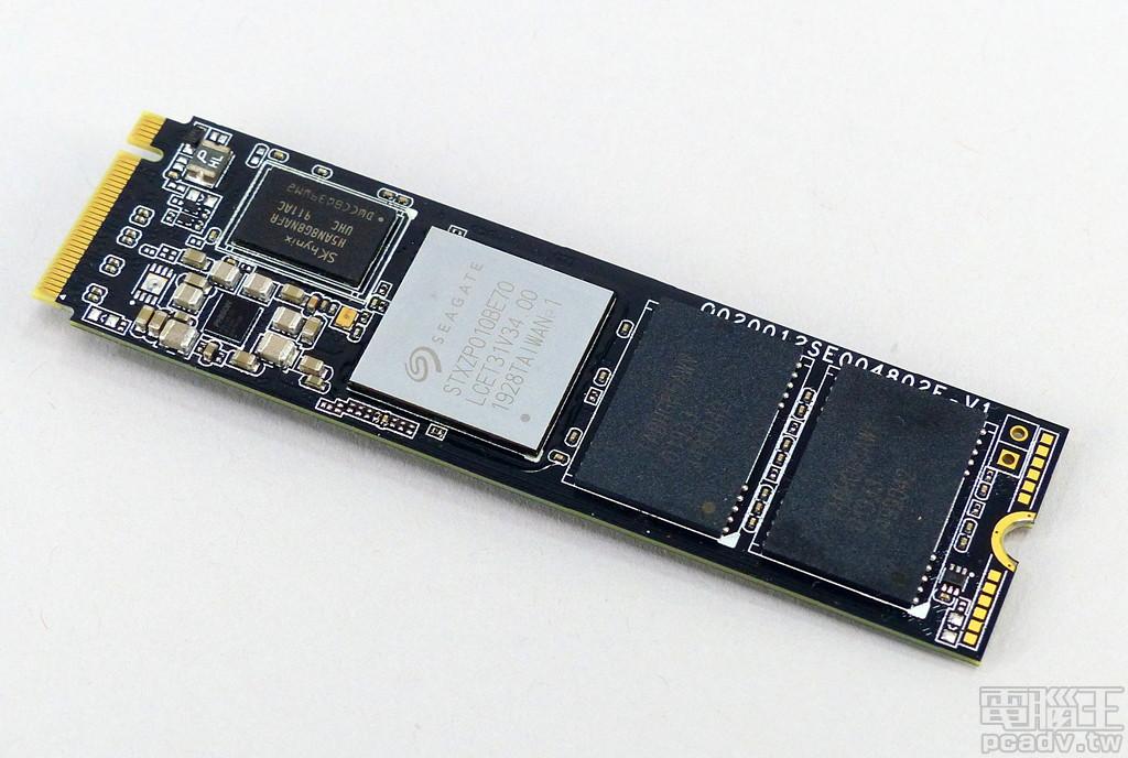 將�面貼紙移除,可以看見內嵌金屬銅片的 SSD 控制器晶片,較小的黑色晶片為動態記憶體,右側 2 個黑色晶片為快閃記憶體。
