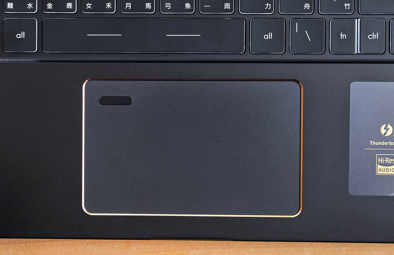 鍵盤下方提供大尺寸無鍵式觸控板,邊緣以鑽切手法搭配金色金屬切面,算是設計上的一個亮點,另外觸控板左上方也整合了指紋辨識器,可快速解鎖系統。